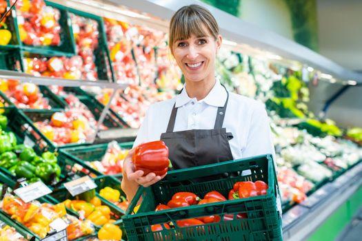 Clerk in a supermarket showing fresh vegetables