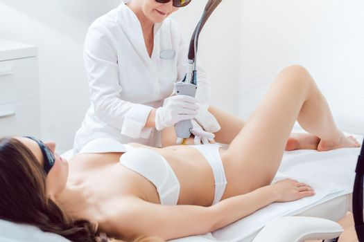 Hair removal in bikini zone using a laser device on young woman