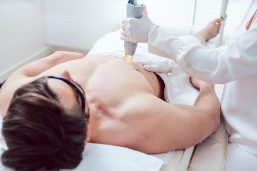 Cosmetologist using laser to remove chest hair of man