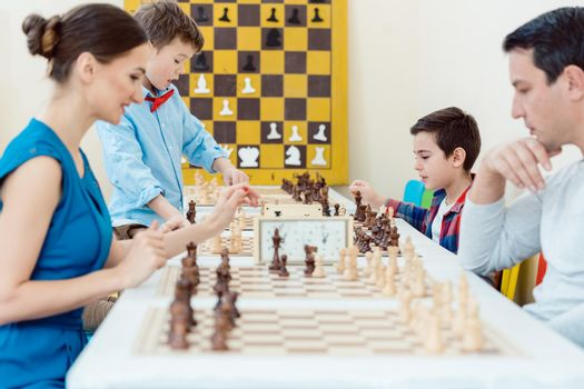 Family playing chess in tournament room