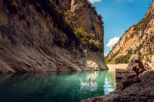 Man jumping into the water of a gorge in the Pyrenees mountains