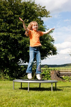 Girl child on trampoline in the garden