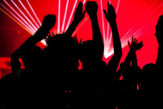 People dancing in club with laser