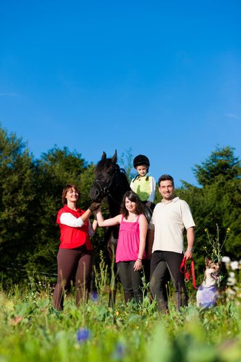 Family and children posing with horse