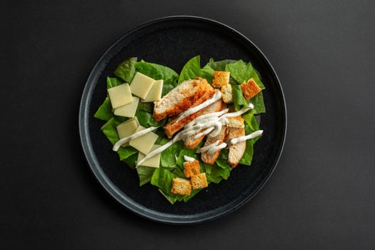 Caesar salad in heart shape love food concept, black stone luxury plate, top view flat lay design, black background