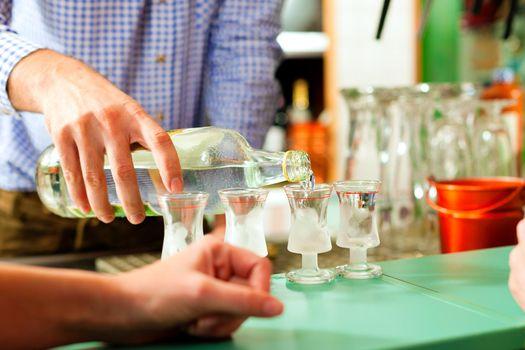 Barkeeper pouring hard liquor in glasses