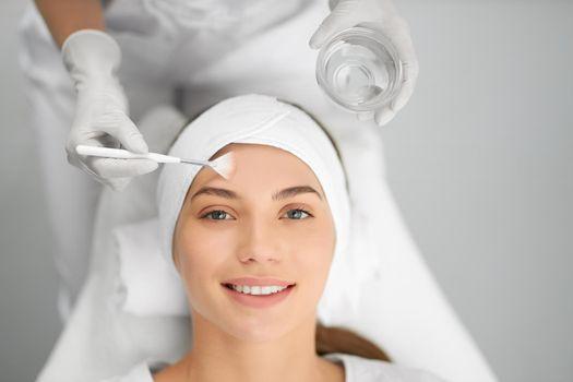 Smiling woman on beauty procedure in beautician.