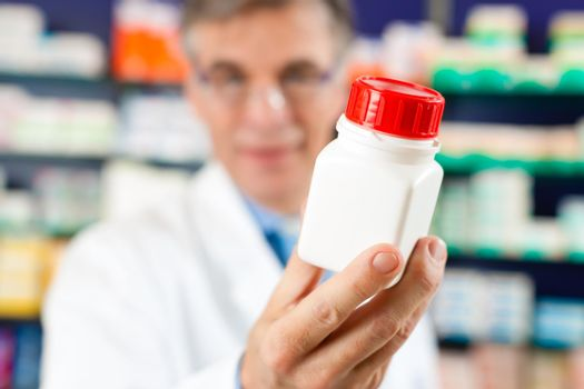 Pharmacist in pharmacy with medicament