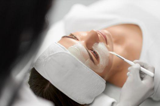 Young woman on procedure peeling face in beauty salon.
