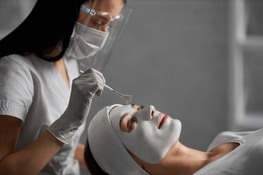 Woman lying on procedure for cleaning face in beautician.