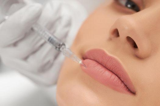 Woman lying on procedure for lip augmentation.