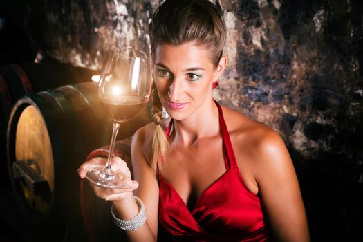 Woman in wine cellar with barrels tasting
