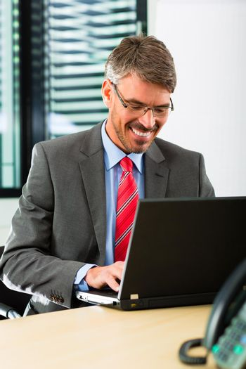 businessperson with laptop in his business office