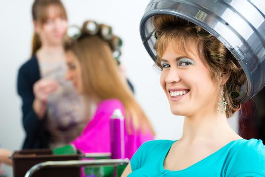 Women at the hairdresser curling hair