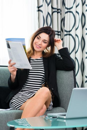 businesswoman in hotel reading a journal