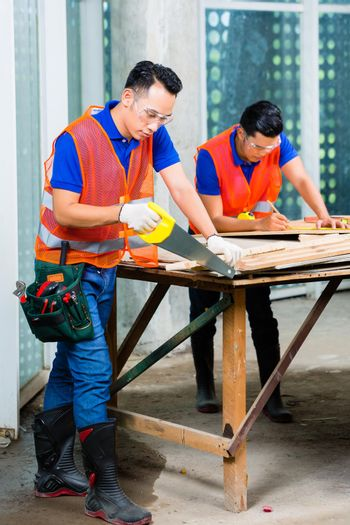 Builder sawing a wood board of building or construction site