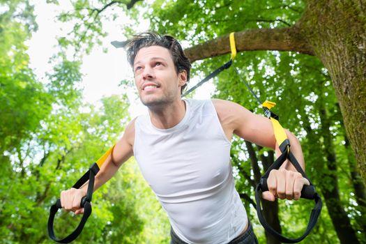 man doing suspension trainer sling sport