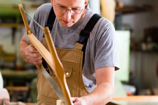 Carpenter using hand saw