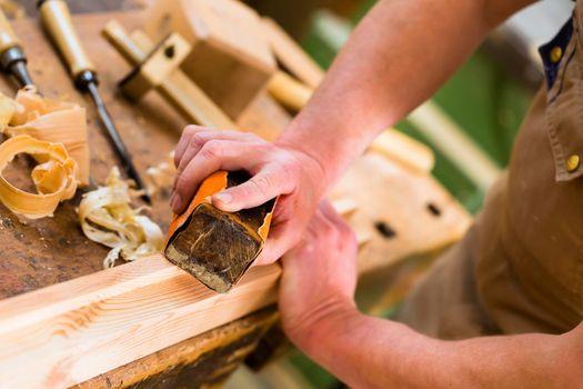 Carpenter with sanding block in carpentry