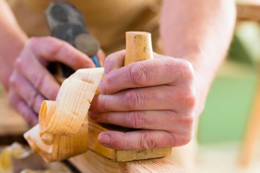Carpenter with wood planer and workpiece in carpentry