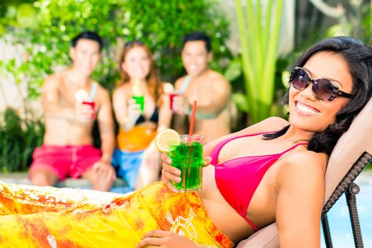 Asian friends partying at pool party in resort