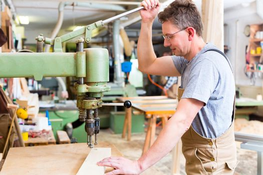 Carpenter using electric drill in carpentry