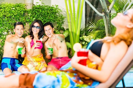Asian friends partying at pool party in hotel