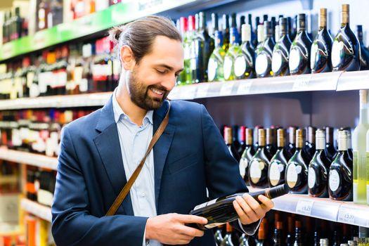 Man selecting wine in liquor store