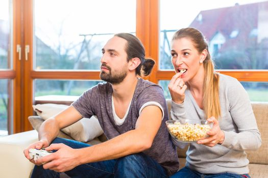 Couple video gaming and having popcorn