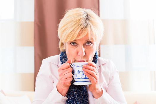Senior drinking tea to cure her flu