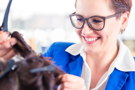 Hairdresser styling woman hair in shop