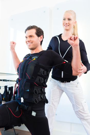 Man having ems training with personal trainer