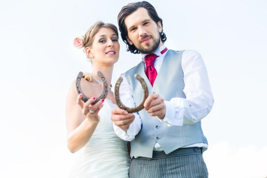 Wedding couple showing horse shoe for luck