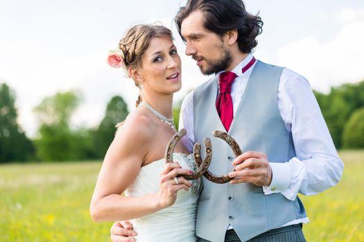 Wedding couple showing horse shoe