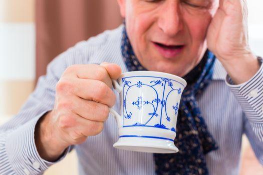 Senior drinking tea to cure flu