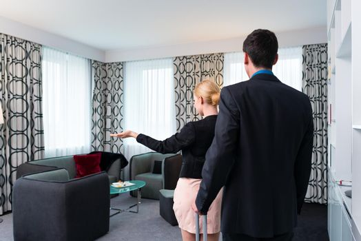 Man and woman arriving  in hotel room