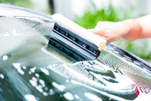 man cleaning windscreen while car wash