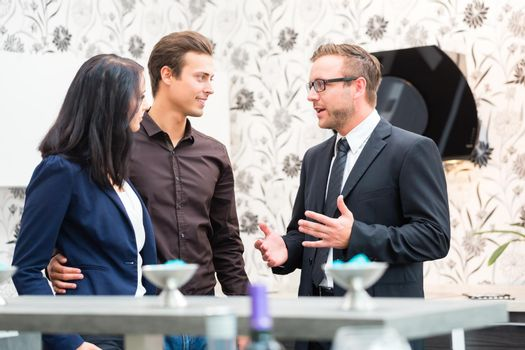 Couple consulting salesman for domestic kitchen