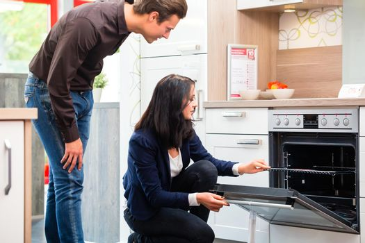 Couple buying domestic kitchen in showroom