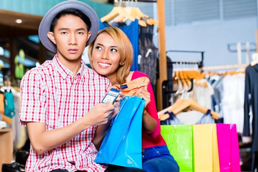 Asian couple with expensive purchase in shop