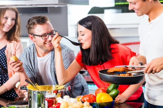 Friends cooking pasta and meat in domestic kitchen