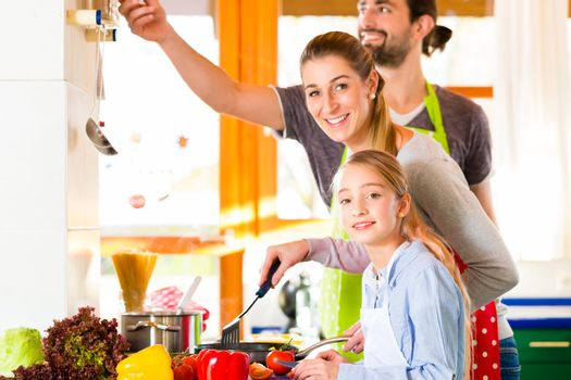 Family cooking in domestic kitchen healthy food