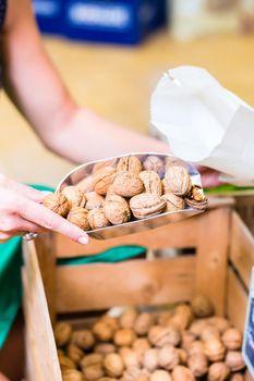 Corner shop clerk filling nuts bags