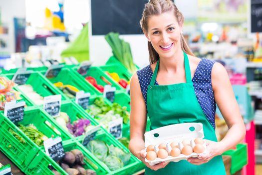 Organic grocery shop clerk offering eggs