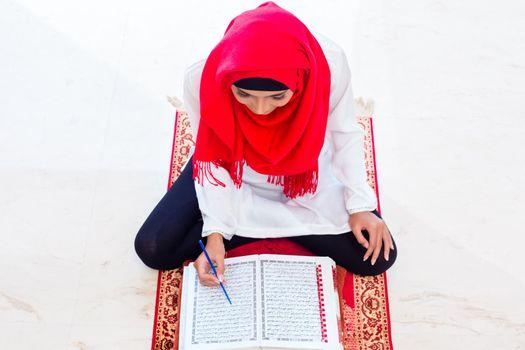 Asian Muslim woman studying Koran or Quran