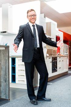 Salesman in domestic kitchen furniture showroom