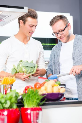 Friends cooking vegies and meat in domestic kitchen