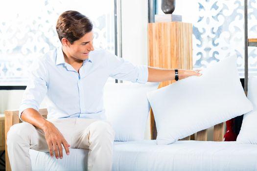 Man buying sofa in furniture store showroom