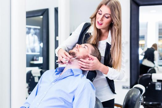 Man being shaved by barber woman