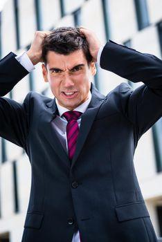 Angry business man tearing hair in despair